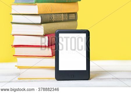 Reading. E-book Reader And A Stack Of Books On A Yellow Background. Mock Up. Concept Of Education An