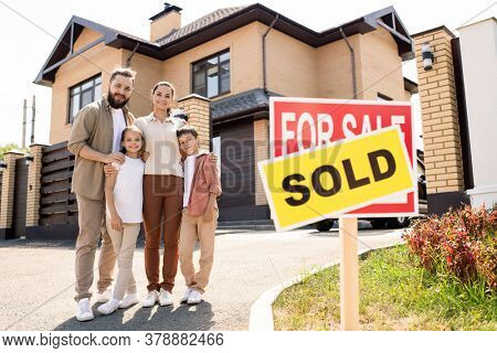 Portrait of smiling young family with two kids embracing each other against new house, moving into new house concept