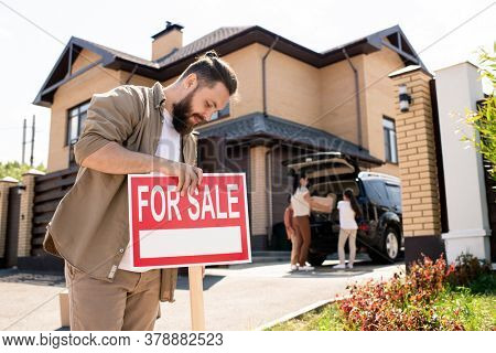 Serious bearded man in casual shirt placing For sale sign against house to pay attention of buyers