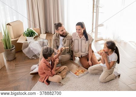 Above view of happy young family with two children sitting on floor and enjoying first dinner in new house