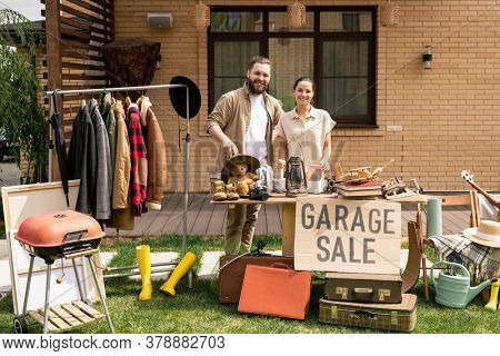 Portrait of cheerful young couple hosting garage sale in backyard while selling useless stuff before moving