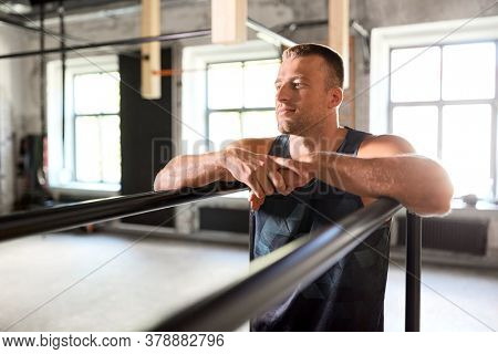 fitness, sport, training and lifestyle concept - young man exercising on parallel bars in gym