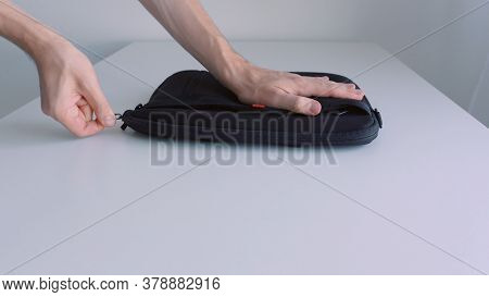 Man Hand Putting Laptop Into A Case, Zipping It Up And Taking Away Of The Table. Action. Close Up Of