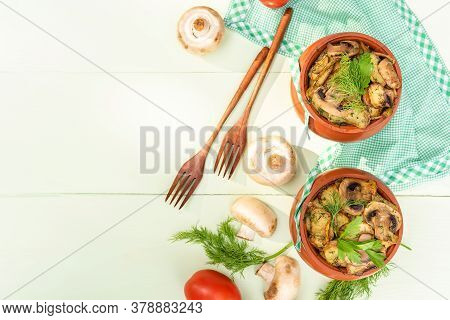 Baked Potatoes In The Oven In A Clay Pot. On A Light Green Background. Top View.
