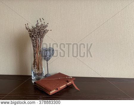 A Glass Vase With Lavender And A Decorative Heart Accentuates The Leather Surface Of The Diary, Crea