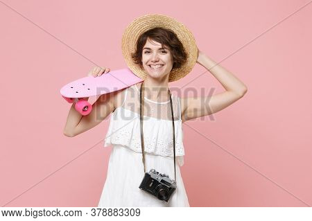 Smiling Young Tourist Girl In Summer Dress Hat With Photo Camera Isolated On Pink Background. Travel