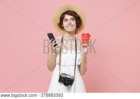 Pensive Tourist Girl In Dress Hat With Photo Camera Isolated On Pink Background. Traveling Abroad To