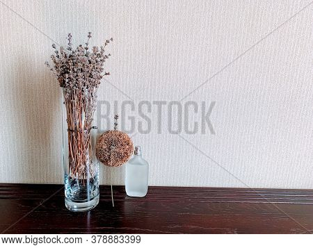 A Lavender Glass Vase And A Decorative Bead Accentuate The Frosted Perfume Bottle, Creating An Inter