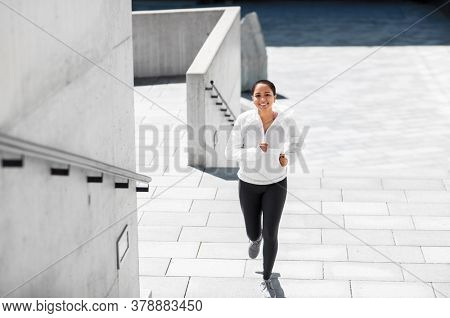 fitness, sport and healthy lifestyle concept - happy smiling young african american woman running upstairs outdoors