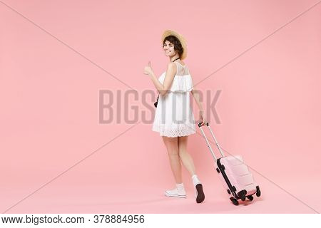 Back Rear View Of Smiling Tourist Woman In Summer Dress Hat With Suitcase Isolated On Pink Backgroun