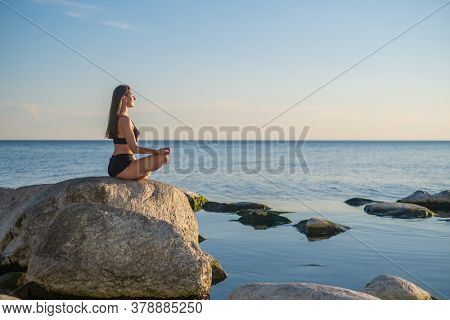 Side view of young female sitting on rock in Lotus pose and meditating against sunset sky during yoga lesson near sea