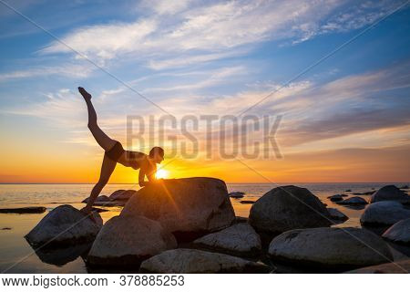 Side view of fit female doing Tree Legged Downward Facing Dog pose on boulders against vivid sundown sky during yoga lesson on seashore