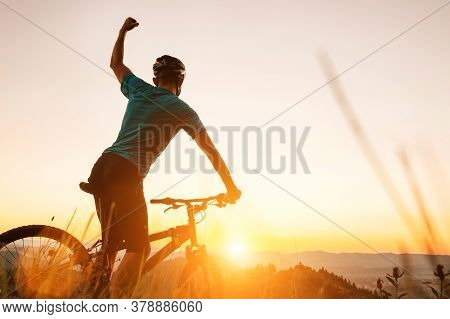 Young Man Biker Man Meets A Sunset In Top Of Hill. He Rising A One Arm Greeting On Another Successfu