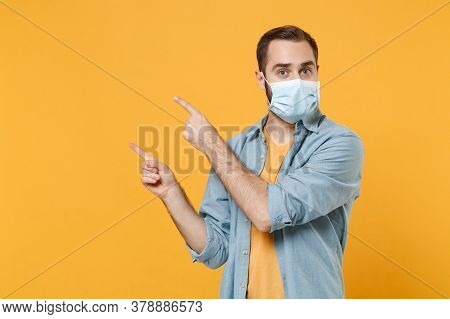 Young Man In Sterile Face Mask Posing Isolated On Yellow Background Studio Portrait. Epidemic Pandem