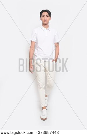 Full body Young handsome man with wearing white polo shirt with white jeans pants runway, in studio