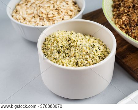 Shelled Hemp Seeds Superfood In White Bowl Over Gray Background.