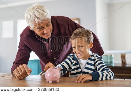 Happy smiling grandson adding money in piggy bank with grandfather. Senior man and cute boy putting coin into pink piggybank at home. Excited boy saving money with help of grandpa.