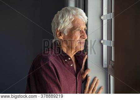 Lonely old man in contemplation near window looking away and thinking. Thoughtful retired man at home looking at view outside window and contemplating. Pensive senior standing and relaxing copy space.