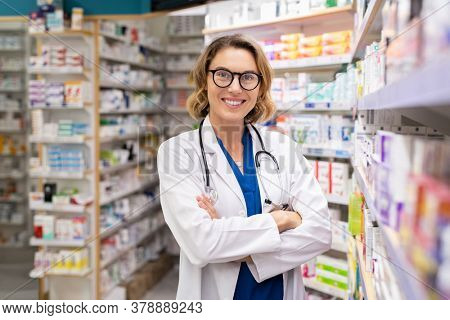 Portrait of mature woman pharmacist at pharmacy wearing labcoat with stethoscope. Happy smiling doctor standing in modern pharmacy drugstore. Friendly young pharmacist owner looking at camera.