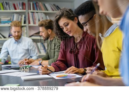 Businesswoman training young business man while explaining graph. African businessman analyzing report with team. Group of multiethnic creative business people sitting while working at financial plan.