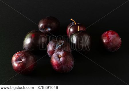 Stack Of Purple Plums On Black Background.