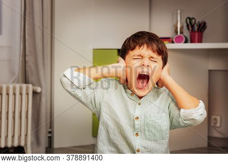 Little Autistic Boy With Strong Negative Face Expression Closing Ears And Loudly Screams
