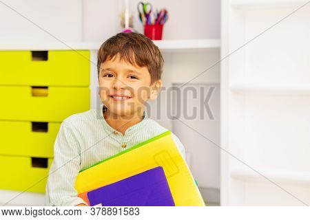 Close Portrait Of Smiling Calm Little Boy Sit In His Room Holding Textbooks With Positive Expression