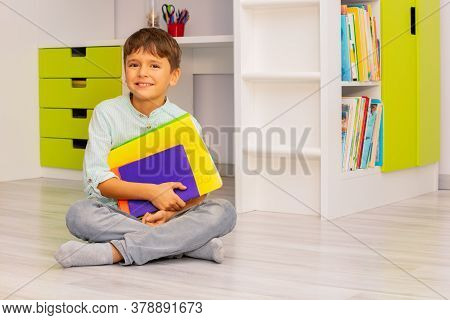 Smiling Calm Little Boy Sit In His Room Holding Textbooks With Positive Expression