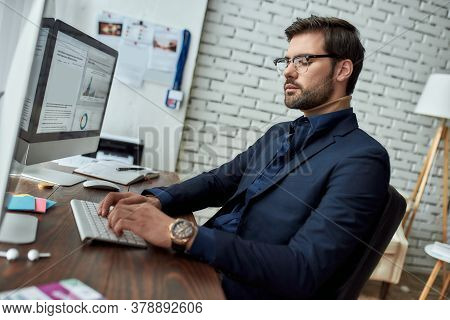 Side View Of A Financial Analyst Wearing Eyeglasses Working With Statistical Data, Sitting At His Wo