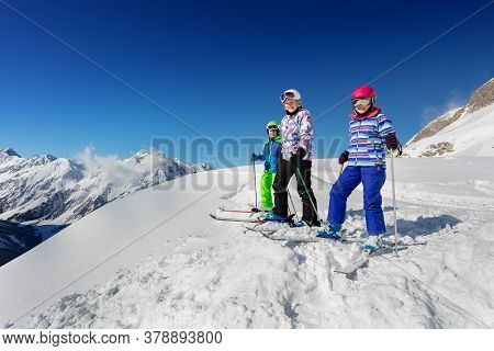 Group Of Three Kids Stand On The Mountain Top In Snow Wearing Ski Colorful Outfit Over Blue Sky