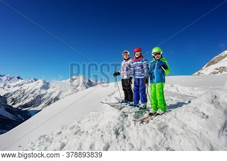Group Of Three Children Stand On The Mountain Top In Snow Wearing Ski Colorful Outfit Over Blue Sky