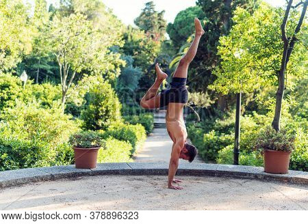 Fitness Man Exercising Handstand In The Park. Street Workout