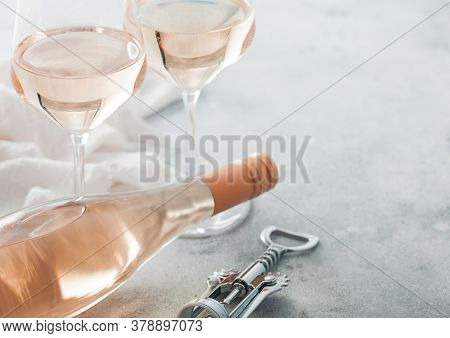Glasses And Bottle Of Rose Pink Wine With Steel Corkscrew On Light Table Background.