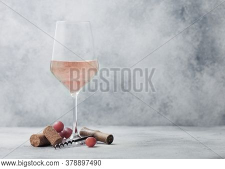 Glass Of Summer Pink Rose Wine With Grapes, Corks And Corkscrew On Light Table Background.