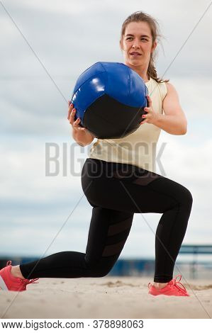 Athletic Woman With Medicine Ball At Outdoor Fitness Gym. Female Athlete Training Legs And Glutes On
