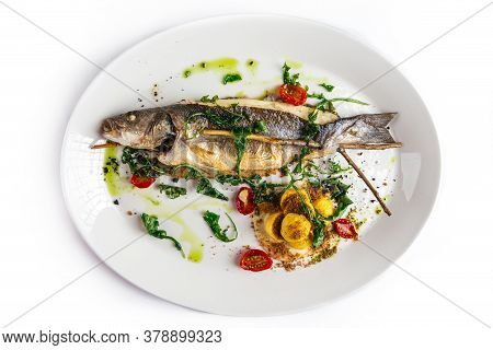 Isolated Sea Bass Fish On A White Plate