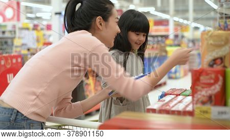 Shopping Concept. Asian Mother And Daughter Are Buying Chocolate Bars In The Mall. 4k Resolution.