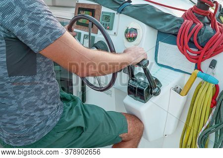 Hand Of Man On The Steering Wheel Sailboat. Hands On The Sailboat's Steering Wheel. Man's Hands With