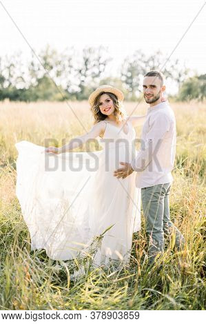 Young Couple, Caucasian Man And His Pregnant Wife In A Field. Happy Family Resting On The Wild Field