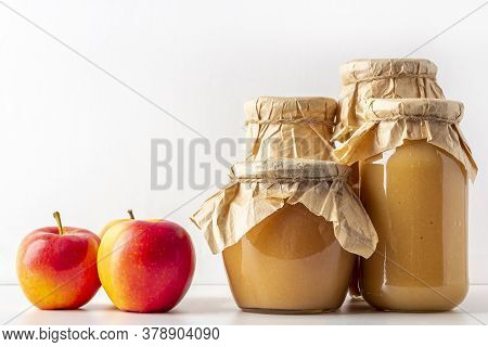 Canned And Preserved Applesauce In Glass Jars On White Table. Fresh Homemade Fruit Puree. Concept Of