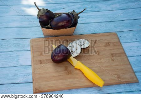 Chopped Eggplants Aubergines And A Yellow Knife On Cutting Board On Wooden Table. Cooking Ingredient