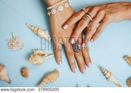 Beautiful Woman Hands With Pink Manicure Holding Sea Shells, Lot Of Rings On Fingers On Blue Backgro