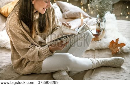 A Young Woman In A Sweater Reads A Book In A Cozy Home.