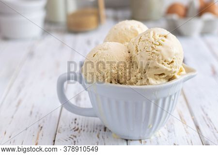 Rustic Homemade Creamy Ice Cream In Ceramic Cup On White Wooden Table