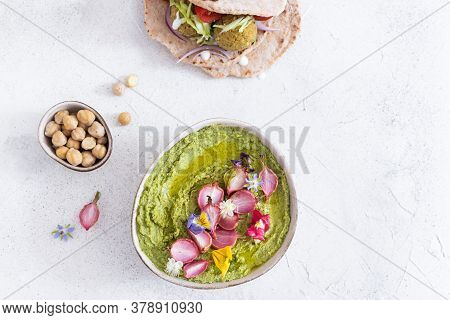 Colorful Green Hummus Bowl With Baked Radish And Edible Flowers, Falafel And Pita Flat Bread, Vegeta