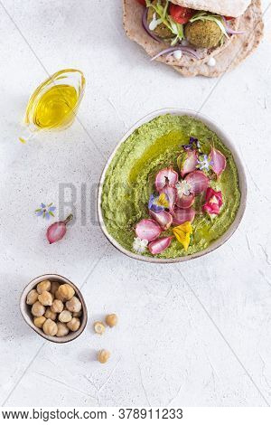 Colorful Green Hummus Bowl With Baked Radish And Edible Flowers, Vegetarian Meal, Top View