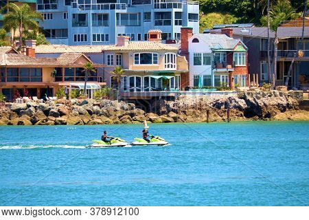 July 30, 2020 In Corona Del Mar, Ca:  People Jet Skiing At A Waterway Out To The Ocean From The Newp