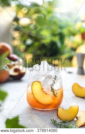 Summer Refreshing Ice Cocktail With Peach Slice And Thyme