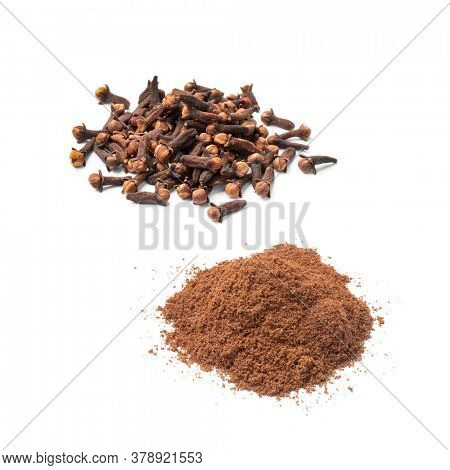 Heap of dried cloves and ground cloves isolated on white background