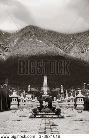 Ancient pagoda in Dali Chongsheng Monastery with snow capped Mt Cangshan, Yunnan, China.